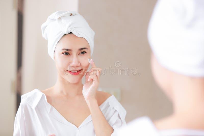 Ung asia kvinna som applicerar fundamentet eller fuktighetsbevarande hudkräm på hennes framsida arkivfoto