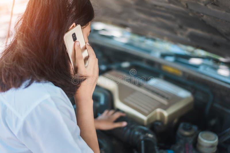 Ung asia kvinna som framme sitter av hennes bil, f?rs?k till att kalla f?r hj?lp med hennes brutna down f?r bil royaltyfria bilder
