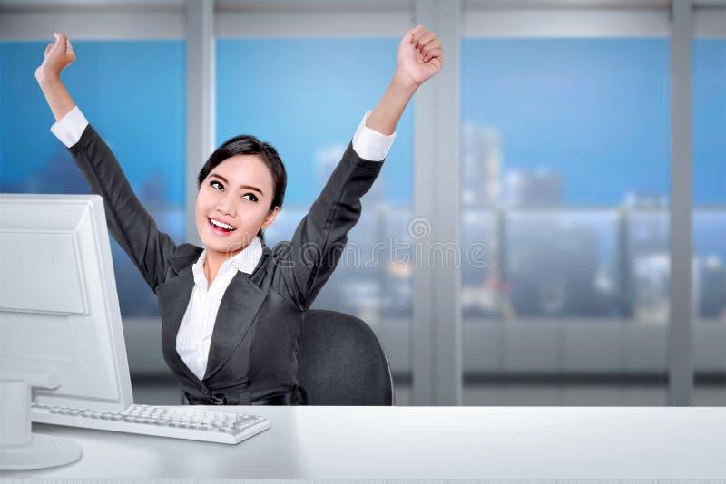 Ung asiatisk affärskvinna med datoren på skrivbordet med lycklig expr arkivbilder