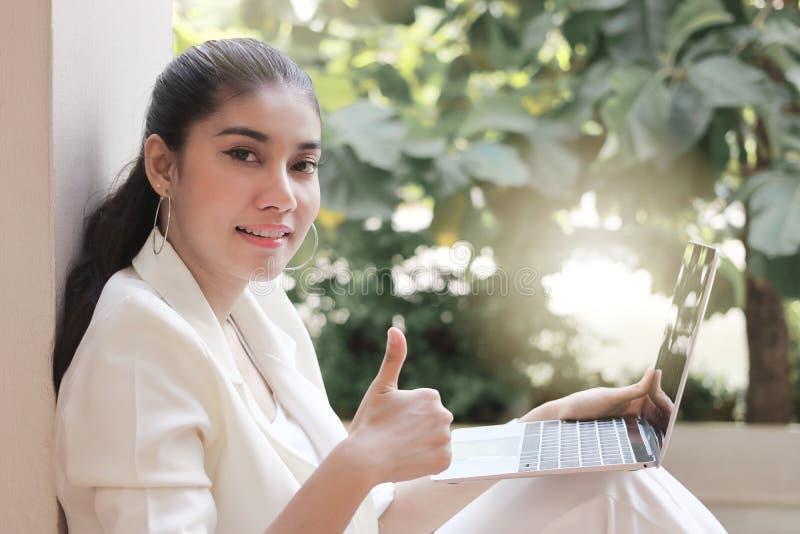 Ung asiatisk affärskvinna med den övre handen för bärbar datorshowtumme Internet av sakerbegreppet royaltyfria bilder