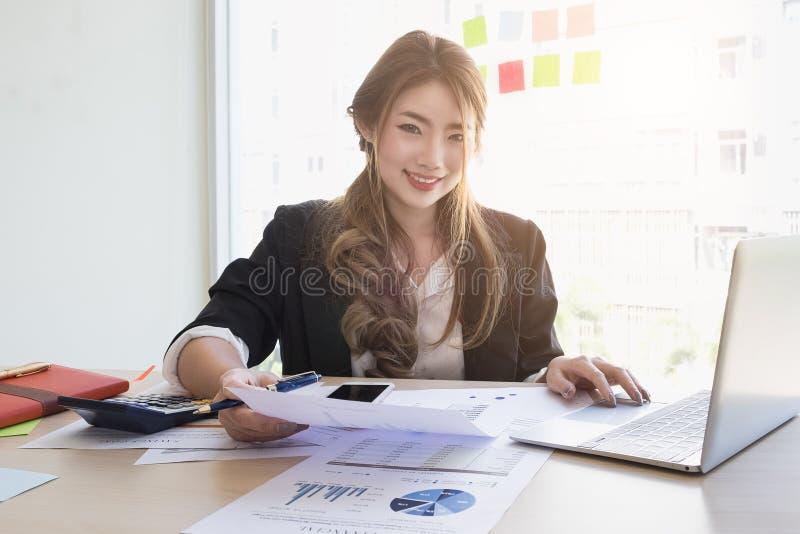 Ung asiatisk affärskvinna som använder den bärbar datordatoren och mobiltelefonen arkivbild