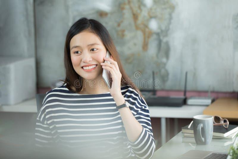 Ung asiatisk affärskvinna som använder smartphonen för att påverka varandra med cust royaltyfri fotografi