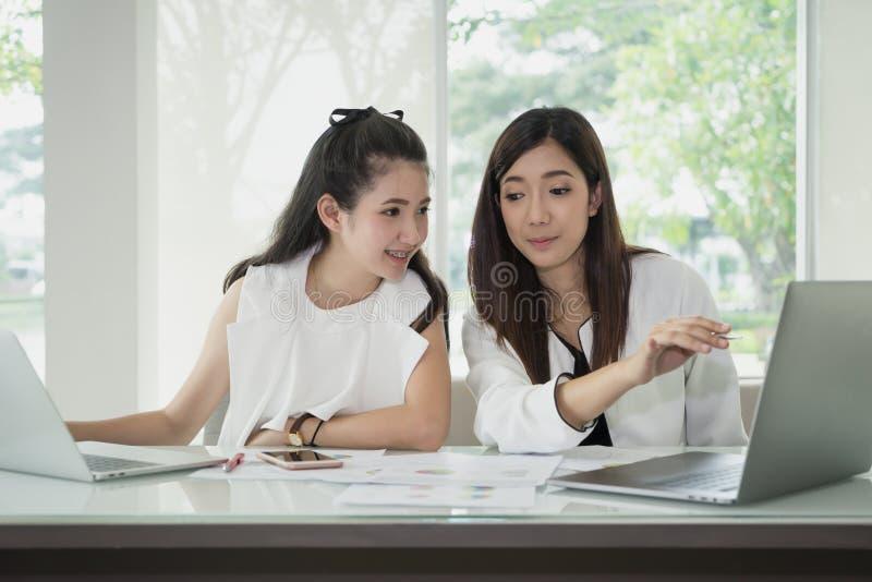 Ung asiatisk affärskvinna som arbetar samman med bärbara datorn på skrivbordet royaltyfria bilder