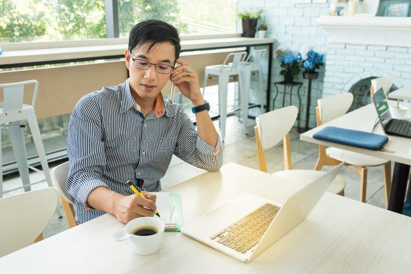 Ung asiatisk affärsman, i för kläderglasögon för tillfällig klänning samtal royaltyfri fotografi