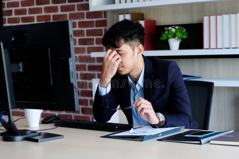 Ung asiatisk affärsman med frustrerat uttryck, medan arbeta med datoren på kontorsskrivbordet, kontorslivsstil royaltyfria bilder