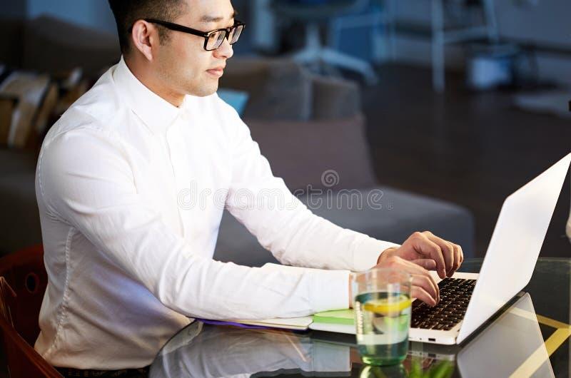 Ung asiatisk affärsman som arbetar med bärbara datorn på kontoret royaltyfria bilder