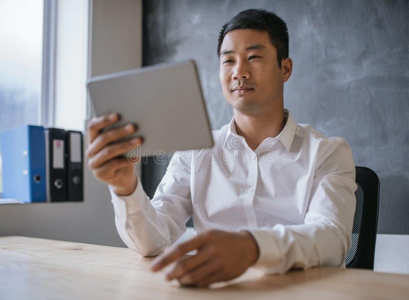 Ung asiatisk affärsman som arbetar på en minnestavla i ett kontor royaltyfri fotografi