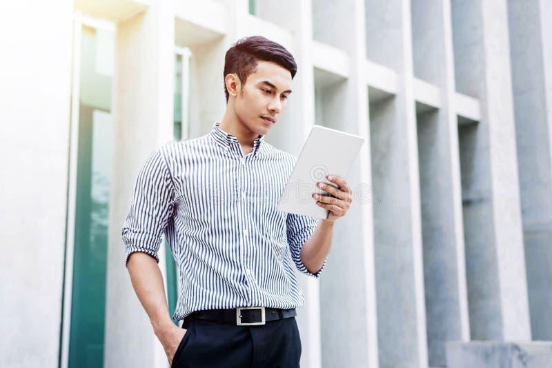 Ung asiatisk affärsman som arbetar på minnestavlan, livsstil av modernt M royaltyfria bilder