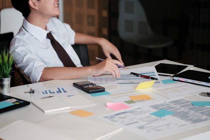 Ung asiatisk affärsman som i regeringsställning sitter, och leende i framsidan, sel arkivfoto