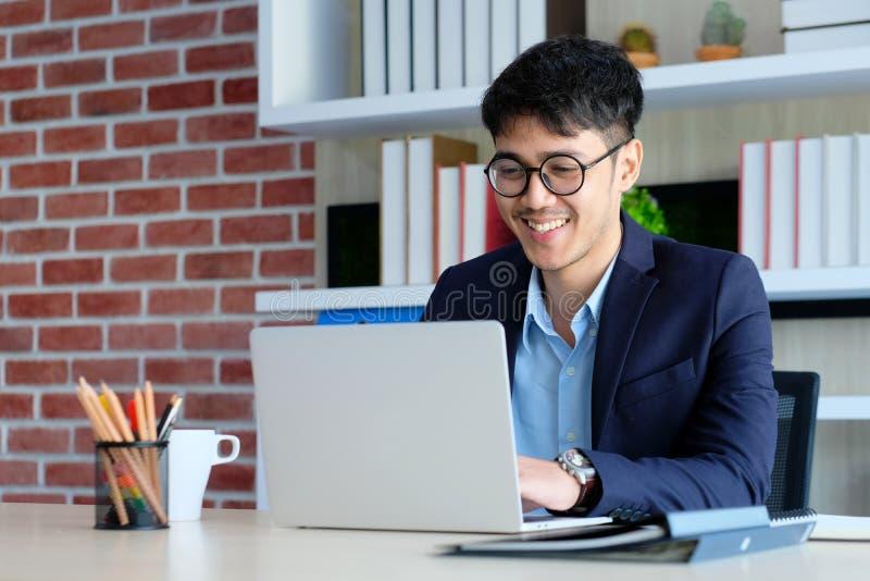 Ung asiatisk affärsman som ler, medan arbeta med bärbar datordatoren på kontoret, begrepp för livsstil för affärskontor royaltyfri fotografi