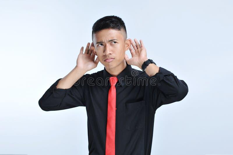 Ung asiatisk affärsman som nästan lyssnar med teckenhanden örat arkivbild