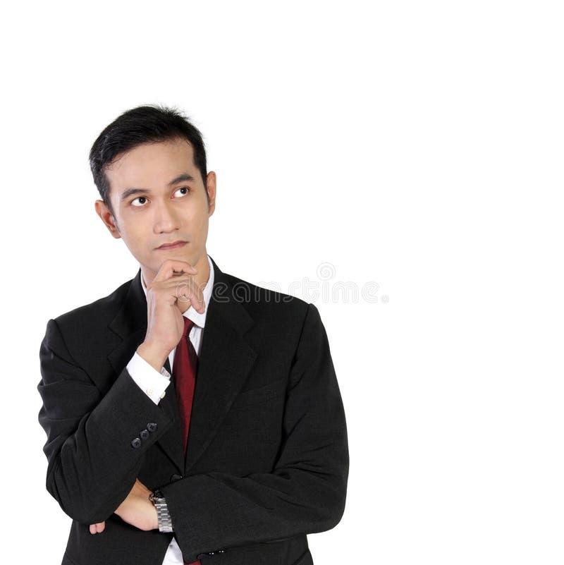 Ung asiatisk affärsman som ser tänka upp, isolerat på vit fotografering för bildbyråer