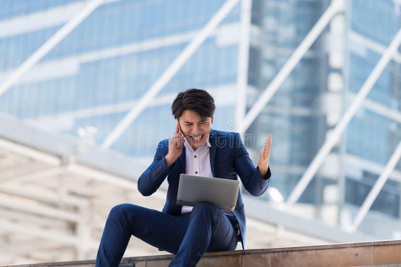 Ung asiatisk affärsman som talar på mobiltelefonen med en allvarlig framsida arkivbild