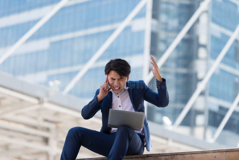 Ung asiatisk affärsman som talar på mobiltelefonen med ett allvarligt f arkivfoton