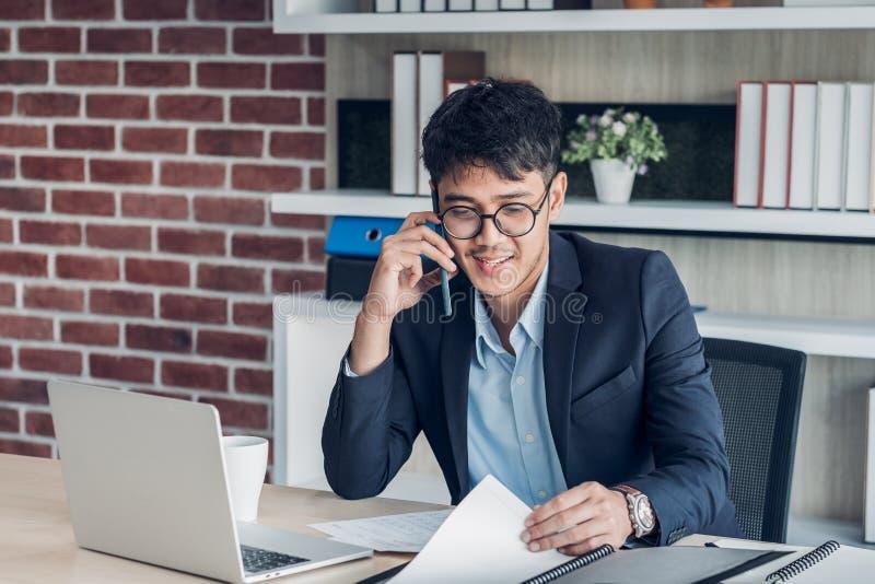 Ung asiatisk affärsmankläderdräkt som talar på mobil och att se skrivbordsarbete, medan arbeta med bärbara datorn på skrivbordtab royaltyfri foto