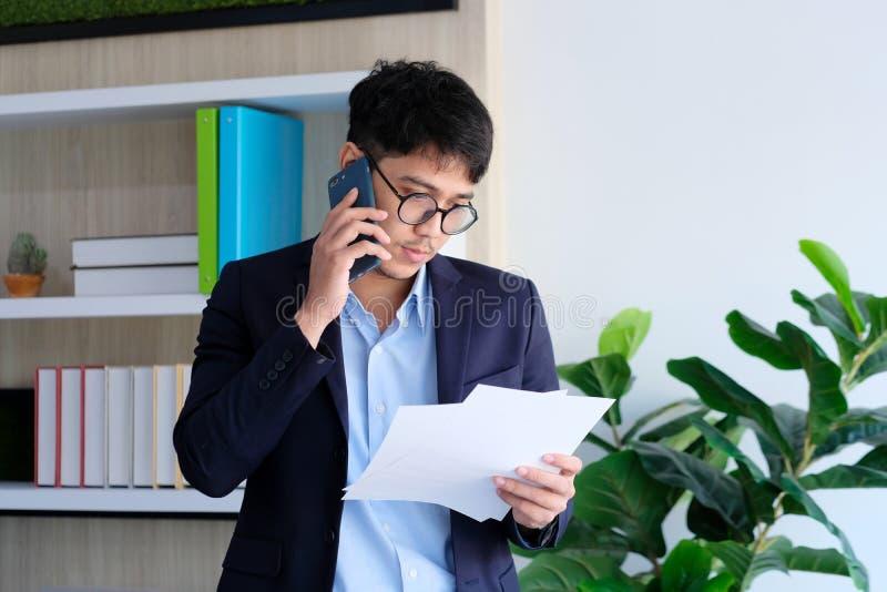 Ung asiatisk affärsmanläsninglegitimationshandlingar som talar telefonen på kontoret, affärskommunikationen och teknologibegreppe royaltyfri fotografi