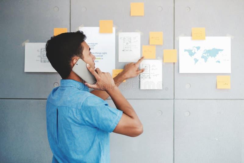 Ung asiatisk affärsmanWorking i regeringsställning mötesrum och samtal via Smartphone Man som analyserar dataplan och projekt arkivfoto