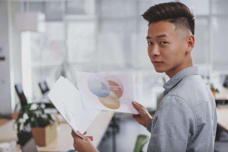 Ung asiatisk aff?rsman som arbetar p? kontoret royaltyfri foto