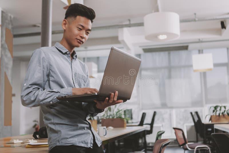 Ung asiatisk aff?rsman som arbetar p? kontoret arkivfoto