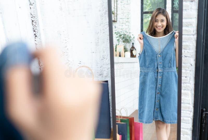 Ung asiatisk attraktiv kvinna som försöker på en blå jeanklänning i ett modelager som ser hennes reflexion i en spegel Att shoppa royaltyfri fotografi