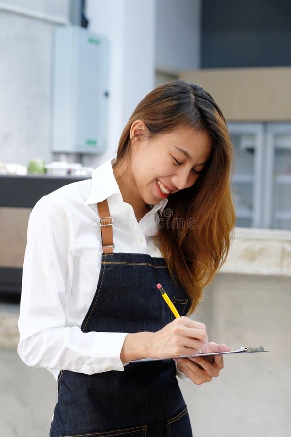 Ung asiatisk barista som tar beställning på kaffekafét med att le fac royaltyfri fotografi