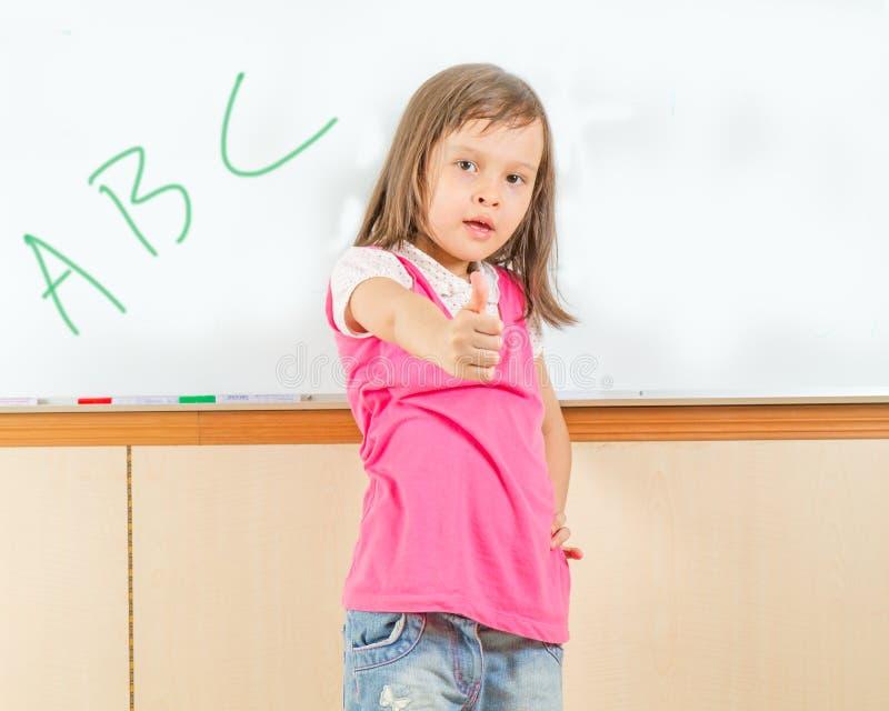 Ung asiatisk barnhandstil på en whiteboard royaltyfri bild
