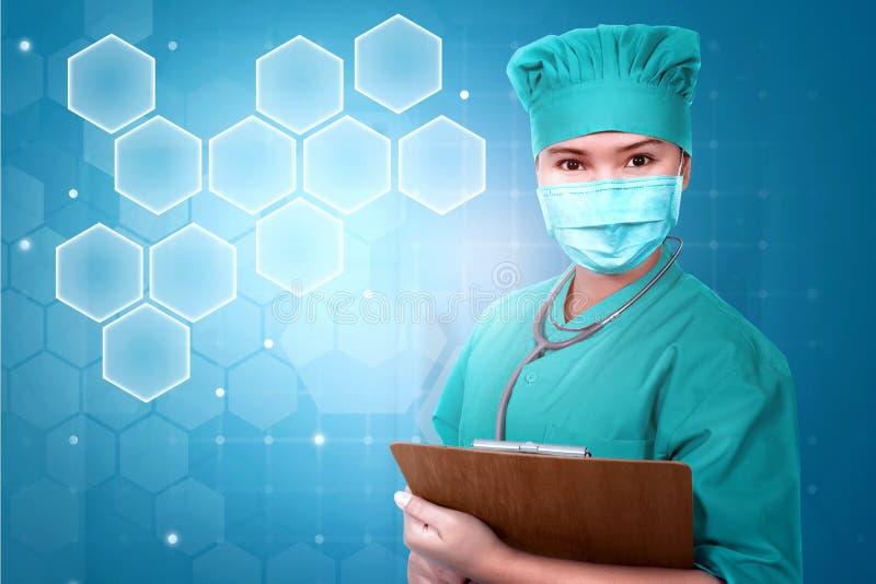 Ung asiatisk doktor i den clipboar framsidamaskeringen och stetoskopet som rymmer royaltyfri bild