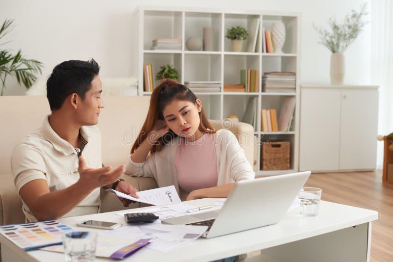 Ung asiatisk familj som argumenterar om finanser arkivbilder