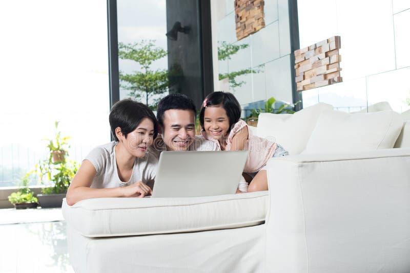 Ung asiatisk familj som tillsammans använder datoren hemma arkivfoton