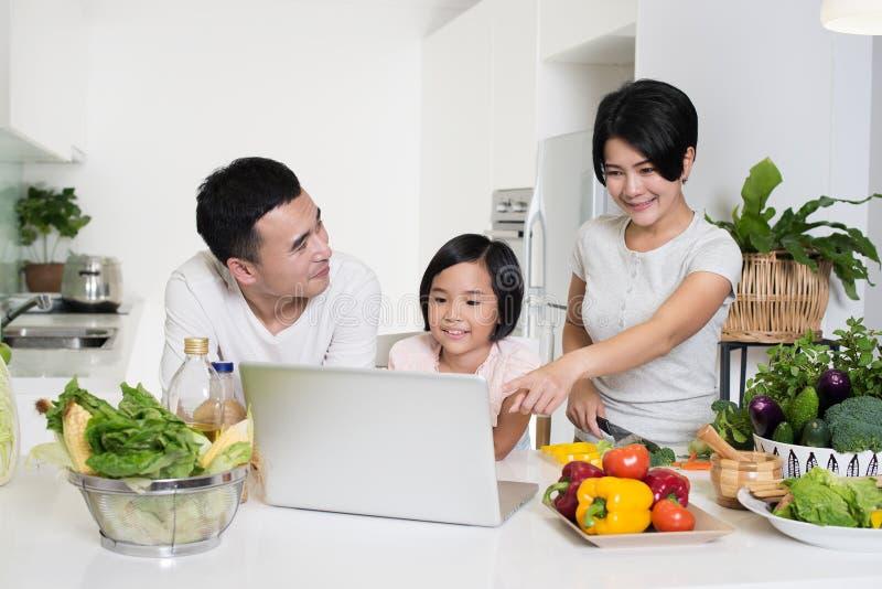 Ung asiatisk familj som tillsammans använder datoren hemma arkivbild