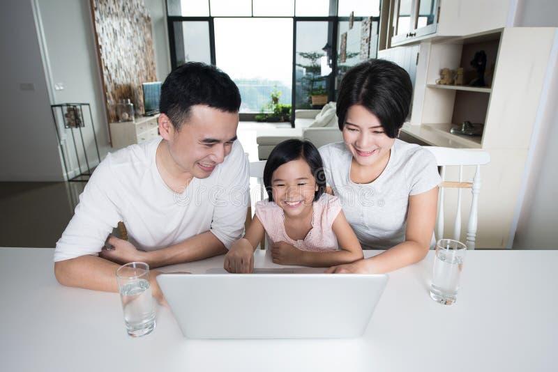 Ung asiatisk familj som tillsammans använder datoren hemma arkivfoto