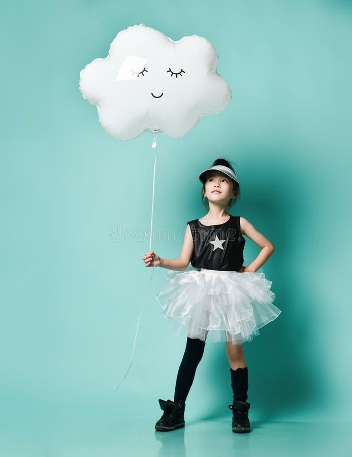 Ung asiatisk flicka i ballongen f?r moln f?r modekjolh?ll den metalliska f?r ungef?delsedag p? den bl?a mintkaramellen royaltyfri fotografi