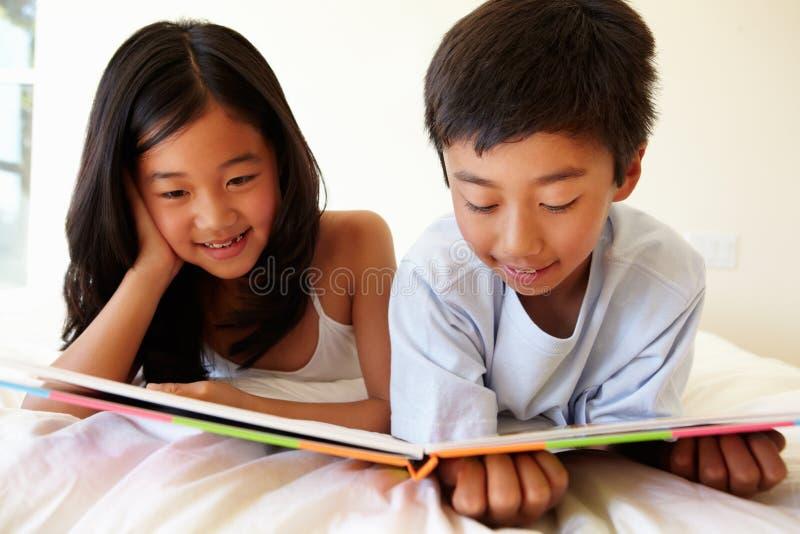 Ung asiatisk flicka- och pojkeläsebok arkivfoto