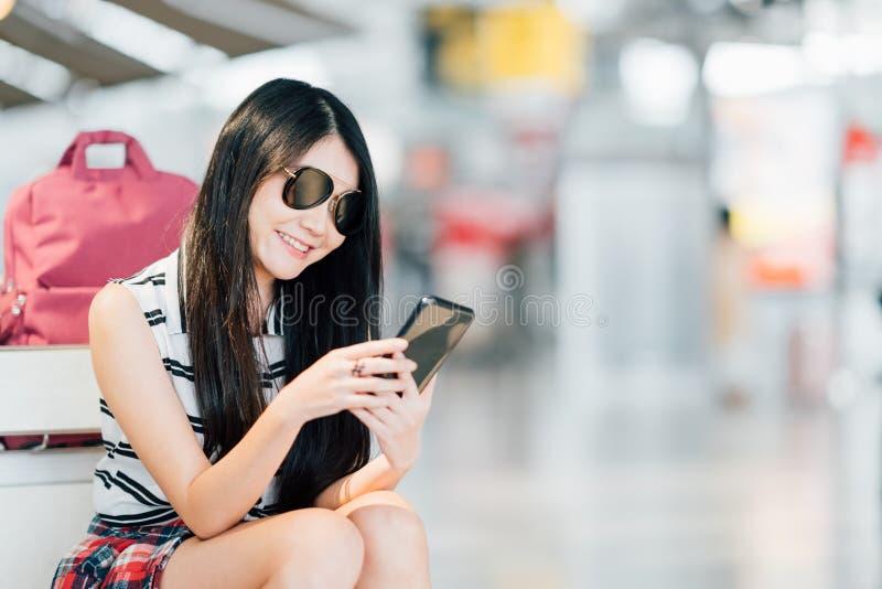 Ung asiatisk flicka som använder smartphonen, väntande på flyg på flygplatsen och att sitta på bagagespårvagnen eller bagagevagne royaltyfria bilder