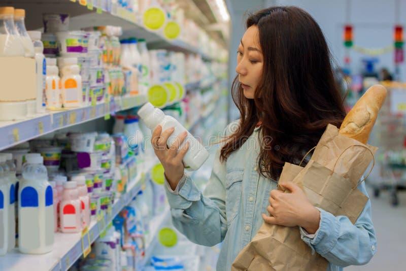 Ung asiatisk flickashopping i en supermarket Kvinnan köper frukt och mejeriprodukten arkivbild