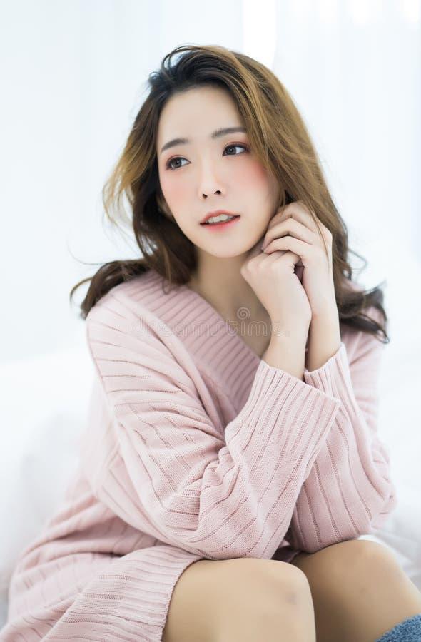 Ung asiatisk härlig kvinna i rosa varm stucken kläder hemma royaltyfri bild