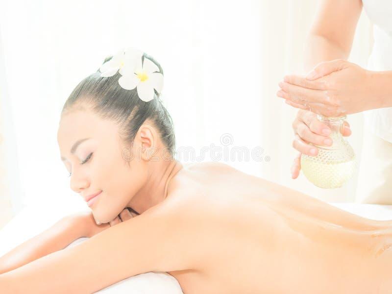 Ung asiatisk härlig kvinna som kopplar av i brunnsortsalong när brunnsort för massagerpåfyllningsolja på hennes kropp arkivfoton