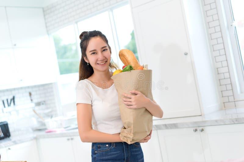 Ung asiatisk härlig kvinnahåll som shoppar den pappers- påsen med grönsaker arkivfoto