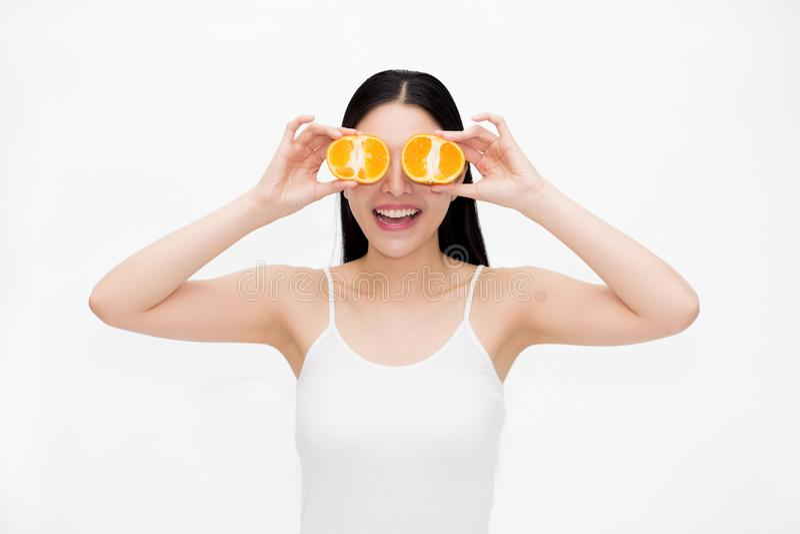 Ung asiatisk härlig le kvinna i innehavstycken för svart hår och vitvästav citrusa apelsiner i gyckel- och lyckasinnesrörelse royaltyfri fotografi