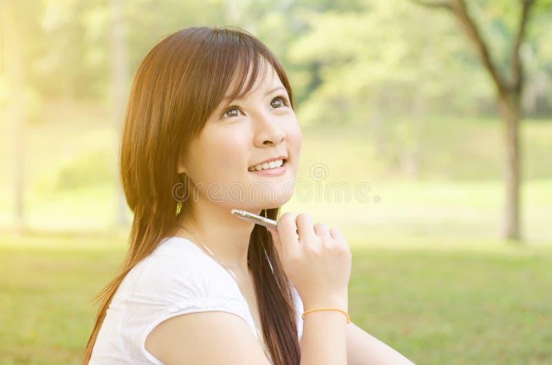 Ung asiatisk högskolaflickastudent som har en tanke royaltyfria bilder