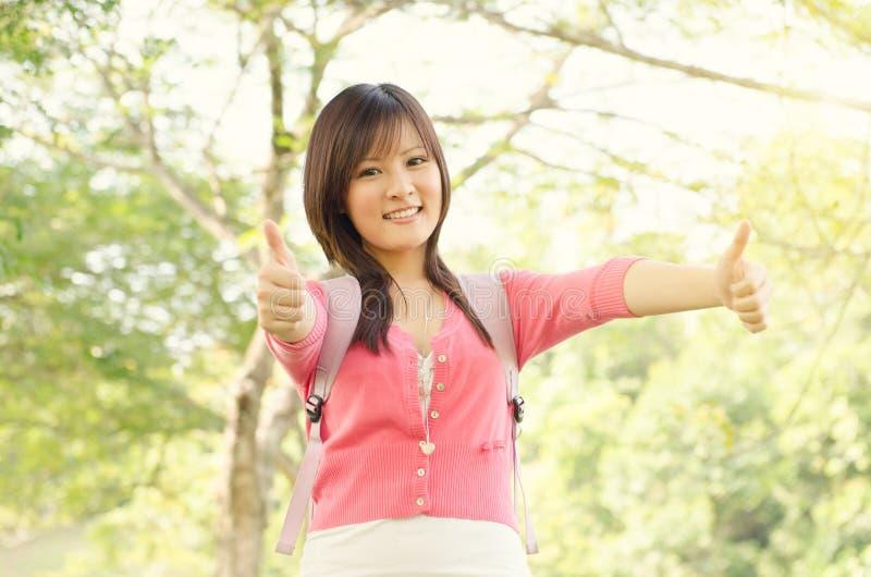Ung asiatisk högskolestudentvisningtumme upp royaltyfria foton