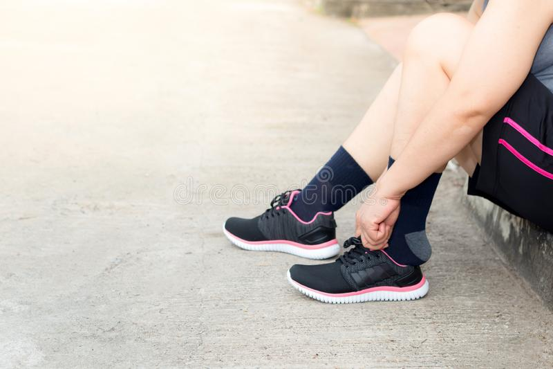 Ung asiatisk idrottsman nenkvinna som binder springskor, den kvinnliga löparen som är klar för att jogga på vägyttersidan, wellne royaltyfri fotografi