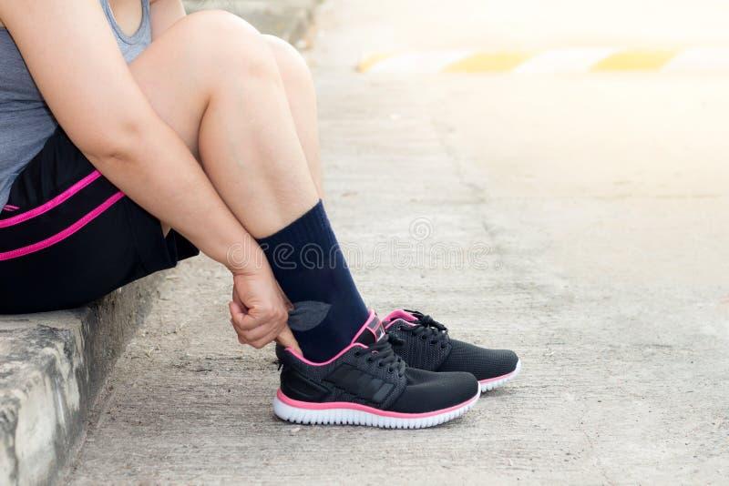 Ung asiatisk idrottsman nenkvinna som binder springskor, den kvinnliga löparen som är klar för att jogga på vägyttersidan, wellne royaltyfria bilder