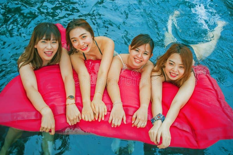 Ung asiatisk kinesisk och koreansk kvinnagrupp av vänner, attraktiva flickvänner på simbassängen för feriesemesterort som har gyc royaltyfria bilder