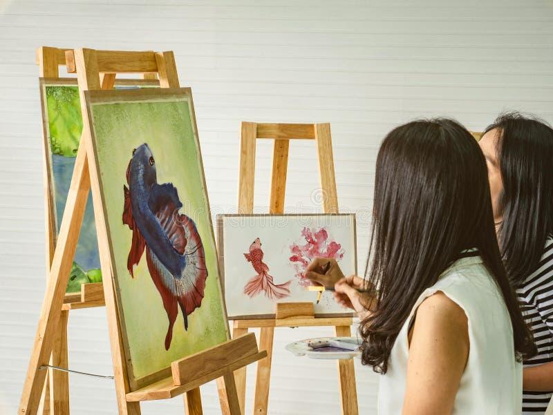 Ung asiatisk konstnär för kvinna som två gryr stund genom att använda idéer att tänka och skapa det bästa konstverket arkivfoton