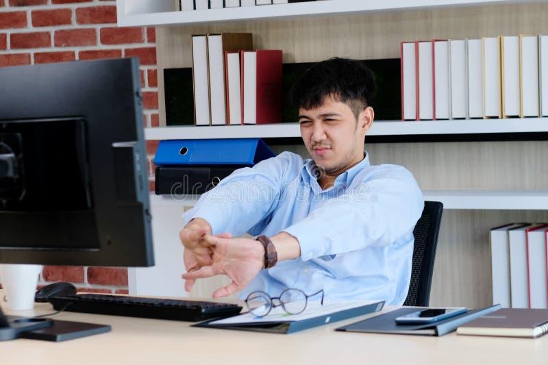 Ung asiatisk kontorsman som sträcker kroppen för att koppla av, medan arbeta med datoren på hans skrivbord, kontorslivsstil, affä royaltyfria bilder