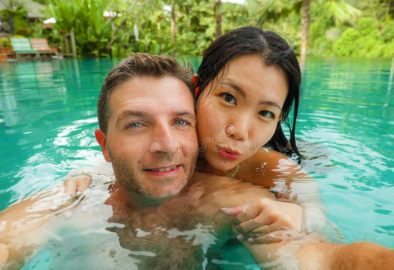 Ung asiatisk kvinna för lyckliga och härliga blandade etnicitetpar och Caucasian man som tar den romantiska selfiebilden på den t royaltyfri foto