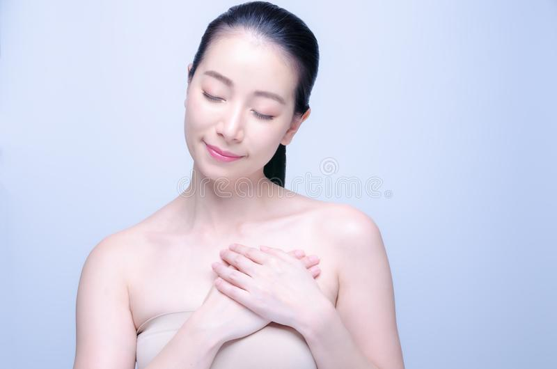 Ung asiatisk kvinna för skönhet som trycker på sund hjärta som isoleras på blå bakgrund K?nslor och f?r?lskelsebegrepp vektor f?r arkivbilder
