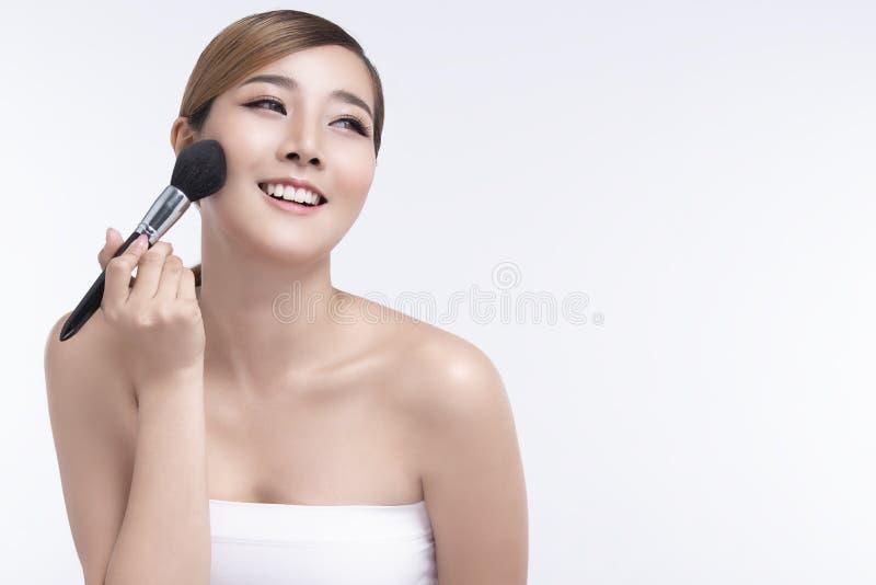 Ung asiatisk kvinna f?r sk?nhet med perfekt ansikts- hud med handen som rymmer kosmetisk rodnad Gester f?r annonseringcosmetology arkivbild