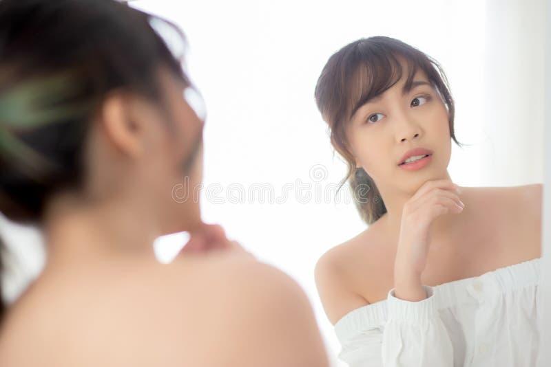 Ung asiatisk kvinna f?r sk?nhetst?ende som ler blick p? spegeln av att kontrollera caucasianen f?r hudomsorg med wellness i sovru arkivbild